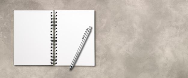 Pusta otwarta spirala makieta notebooka i długopis na białym tle na betonie