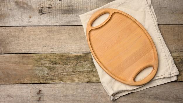 Pusta owalna brązowa drewniana taca na drewnianej powierzchni, widok z góry