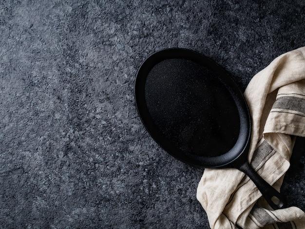 Pusta owalna lana żelazna smaży niecka na zmroku - szarość betonuje tło