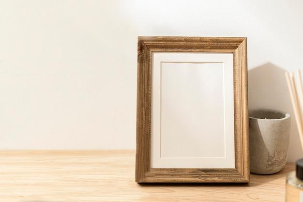 Pusta ozdobna ramka na zdjęcia na drewnianym stole