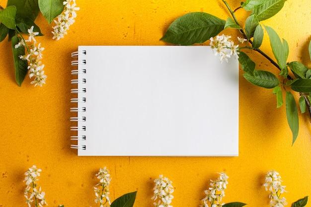 Pusta papierowa karta z ramką z białymi kwiatami kompozycja kwiatowa