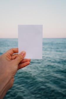 Pusta papierowa notatka w ręku w niesamowitym krajobrazie
