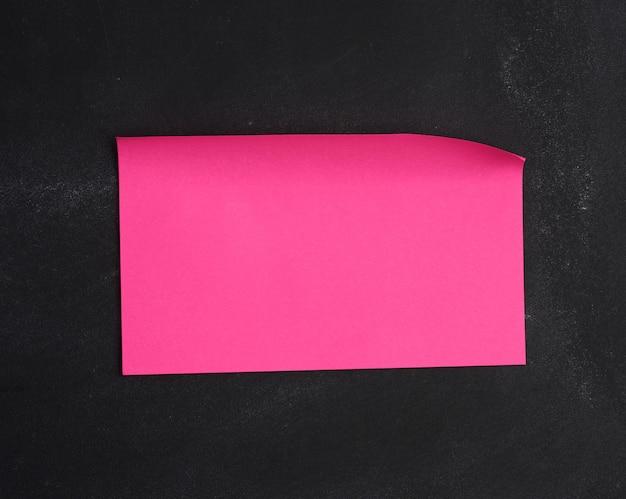 Pusta papierowa różowa naklejka przyklejona na czarnej tablicy