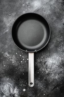 Pusta patelnia z kopią miejsca na tekst lub jedzenie z kopią miejsca na tekst lub jedzenie, widok z góry płasko leżący, na tle czarnego ciemnego kamiennego stołu