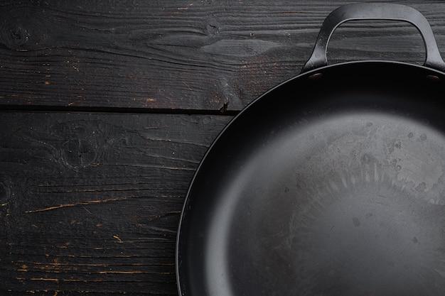 Pusta patelnia żeliwna z miejsca kopiowania tekstu lub jedzenia z miejscem kopiowania tekstu lub żywności, widok z góry płasko leżał, na tle czarnego drewnianego stołu