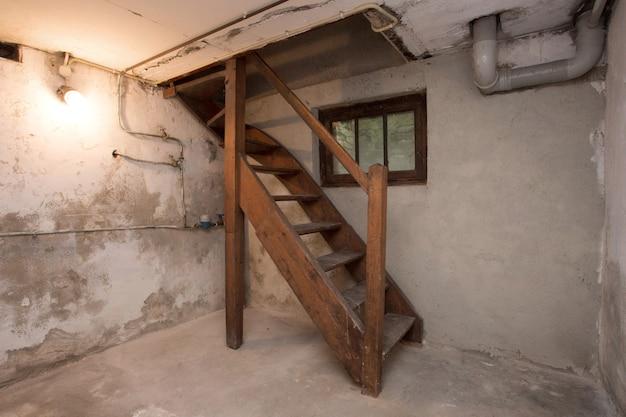 Pusta piwnica w opuszczonym starym budynku przemysłowym z niewielką ilością światła i ciemnością drewnianych schodów