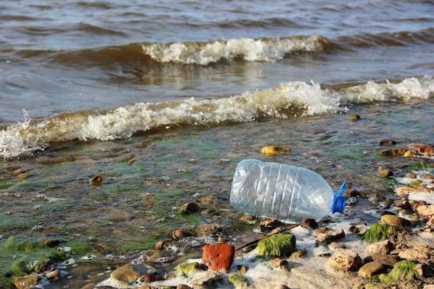 Pusta plastikowa butelka na falach w pobliżu brzegu. śmieci, odpady, zanieczyszczenia i przyroda. t