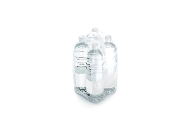 Pusta plastikowa butelka w przezroczystej folii termokurczliwej na białym tle