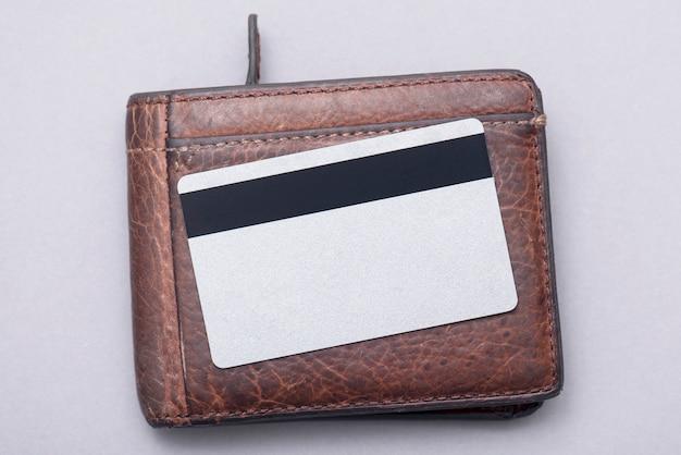 Pusta plastikowa karta kredytowa na brązowym skórzanym portfelu. obraz koncepcji biznesowej