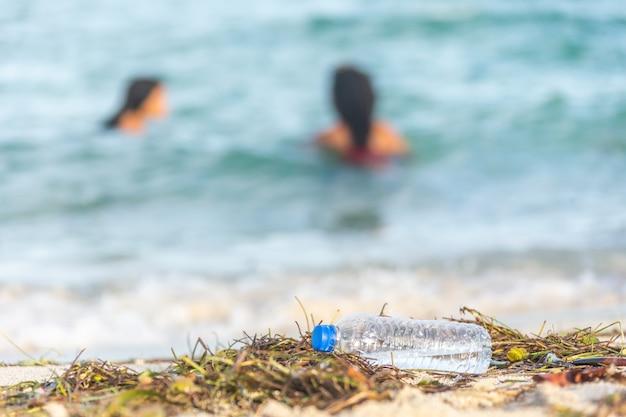 Pusta plastikowa plaża z butelkami wody wypełniona wodorostami, śmieciami i odpadami na brudnej, piaszczystej plaży z ludźmi na morzu