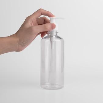Pusta plastikowa przezroczysta butelka z dozownikiem airless pompka z etykietą i reklamami żelu, mydła, alkoholu, kremów i kosmetyków.