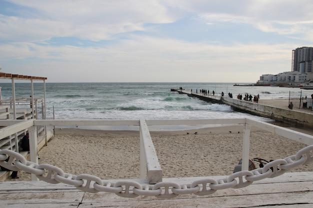 Pusta plaża morza czarnego w pochmurną jesienną pogodę. krajobraz z burzowymi falami morskimi rozbija się o pustą dziką plażę na pochmurnym niebie w pochmurny dzień.