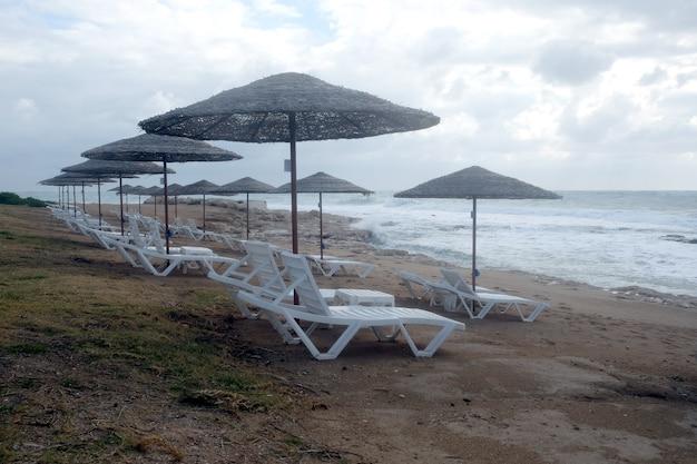 Pusta plaża nad morzem pod koniec sezonu wypoczynkowego z wieloma pustymi leżakami i parasolami wieczorem na tle nadchodzących fal morskich