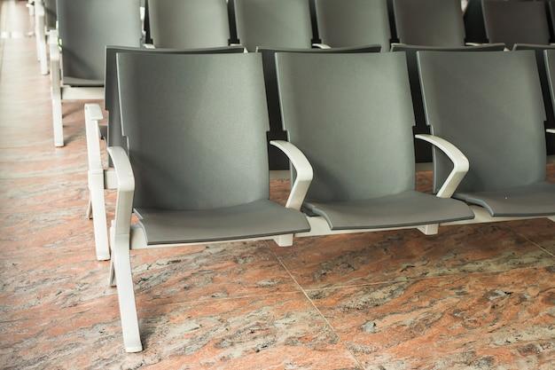 Pusta poczekalnia terminalu lotniska z krzesłami.