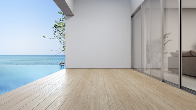 Pusta podłoga tarasu w pobliżu salonu i białej ściany w nowoczesnym domu na plaży
