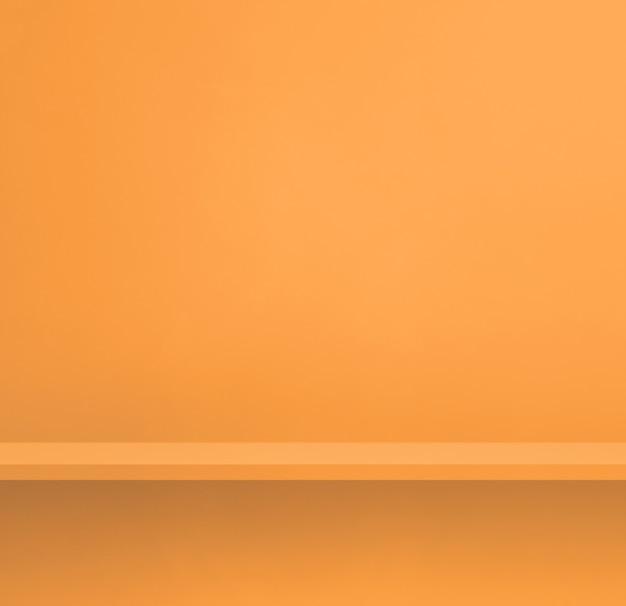 Pusta półka na jasnopomarańczowej ścianie. scena szablonu tła. kwadratowy baner