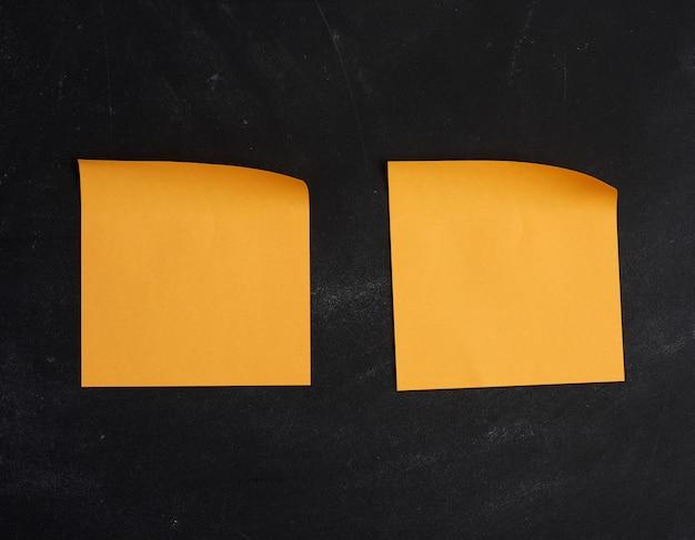 Pusta pomarańczowa papierowa naklejka przyklejona na czarnej tablicy