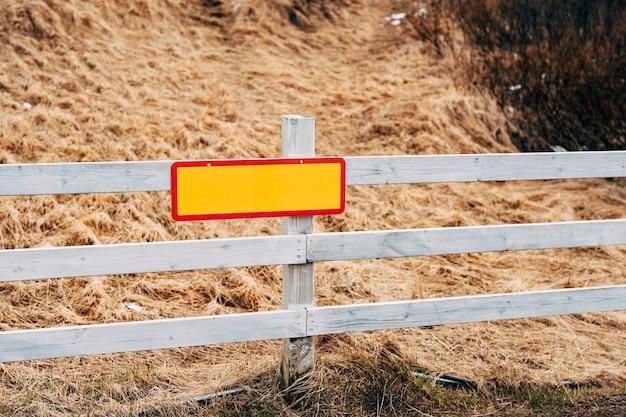 Pusta pomarańczowa tablica wyników z czerwoną obwódką wisząca na drewnianym płocie