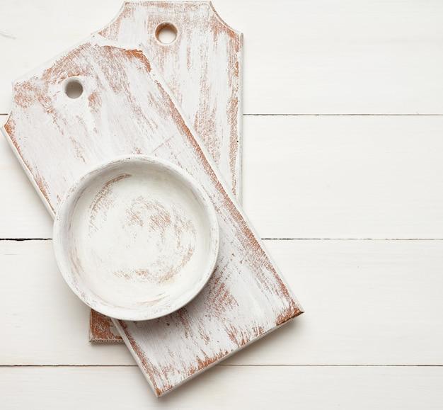 Pusta prostokątna biała deska do krojenia i okrągły talerz na drewnianej przestrzeni