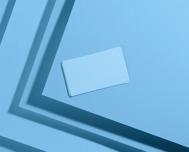 Pusta prostokątna wizytówka na kreatywnym niebieskim tle z arkuszy papieru z cieniem, widok z góry