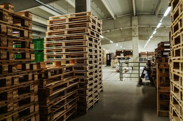 Pusta przestrzeń magazynowa z dużą ilością palet starannie ułożonych w zakładzie fabrycznym
