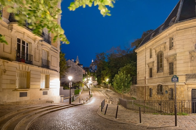Pusta przytulna ulica i bazylika sacre-coeur nocą, dzielnica montmartre w paryżu, francja