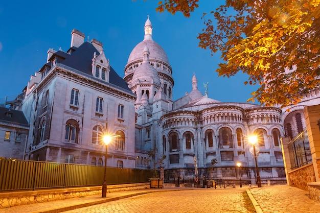 Pusta przytulna ulica i bazylika sacre-coeur podczas porannej niebieskiej godziny, dzielnica montmartre w paryżu, francja