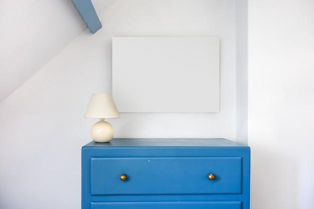 Pusta pusta ramka na zdjęcia i niebieski rustykalny drewniany kredens. tło białe ściany