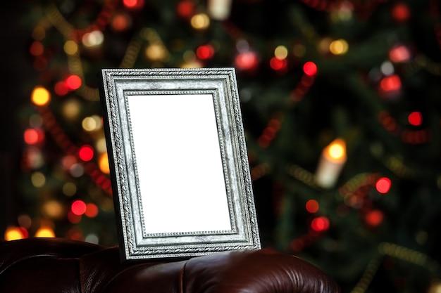 Pusta pusta ramka na zdjęcia w boże narodzenie ozdobione nieostre tło ze światłami zabawek