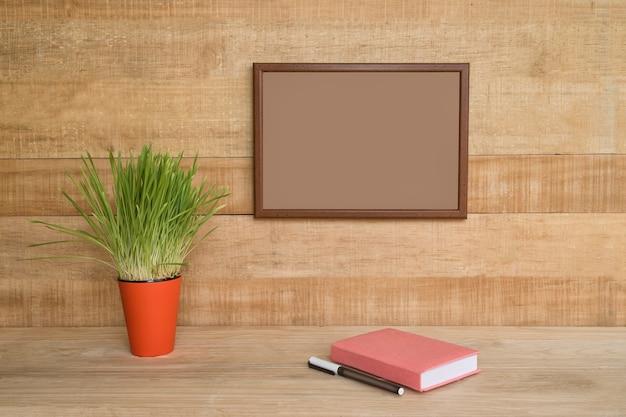Pusta rama na drewnianej ścianie. notatnik i długopis, zielona roślina doniczkowa na stole