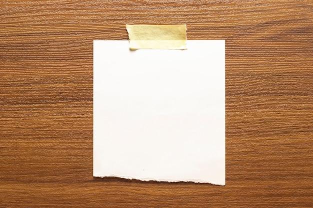 Pusta rama z rozdartego papieru przyklejona taśmą klejącą do drewnianej teksturowanej ściany