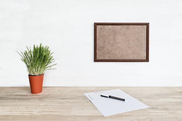 Pusta ramka na białej ścianie. arkusz papieru i długopis, zielona roślina doniczkowa na stole. miejsce do pracy w domu