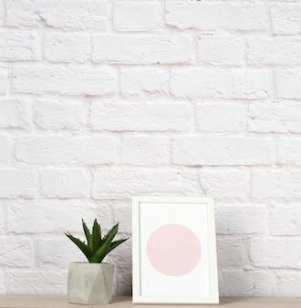 Pusta ramka na zdjęcia, aloes w białej ceramicznej doniczce