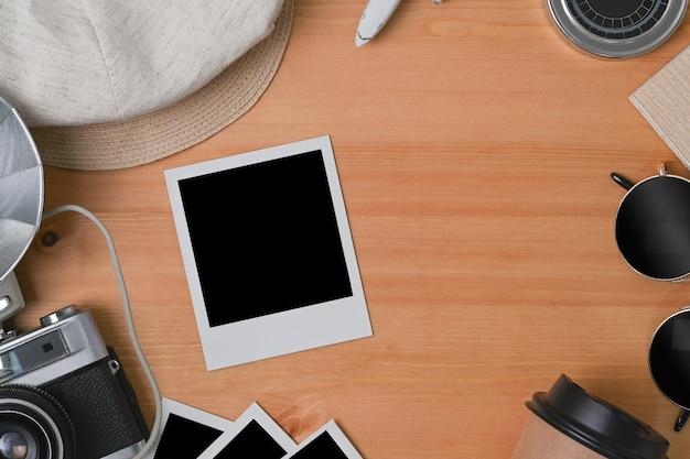 Pusta ramka na zdjęcia, aparat, kubek i okulary na drewniane tła.