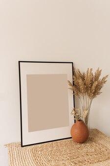 Pusta ramka na zdjęcia, bukiet puszystych trzciny w wazonie, żyto w glinianym garnku na białej ścianie