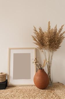 Pusta ramka na zdjęcia, bukiet trzciny w wazonie, żyto w glinianym garnku na białej ścianie