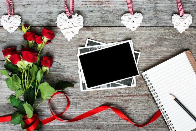 Pusta ramka na zdjęcia i notatnik z czerwonymi różami i ręcznie robionymi drewnianymi sercami
