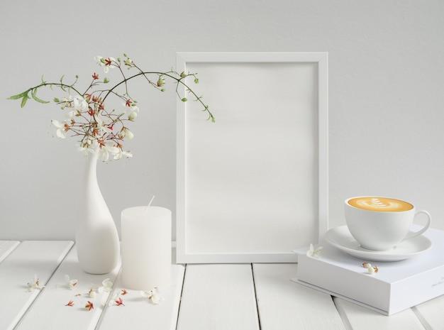 Pusta ramka na zdjęcia makiety, filiżanka kawy, świeca i piękne kiwające kwiaty clerodendron w nowoczesnym ceramicznym wazonie na drewnianym stole z białej powierzchni drewna, śniadanie w białym wnętrzu pokoju