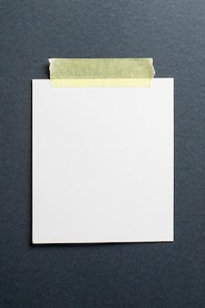 Pusta ramka na zdjęcia polaroid z miękkimi cieniami i żółtą taśmą klejącą na tle czarnego papieru rzemiosła