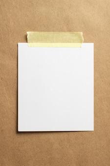 Pusta ramka na zdjęcia polaroid z miękkimi cieniami i żółtą taśmą klejącą na tle papieru tekturowego