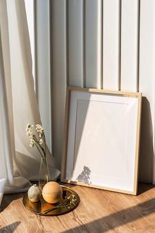 Pusta ramka na zdjęcia przy białej ścianie na drewnianej podłodze