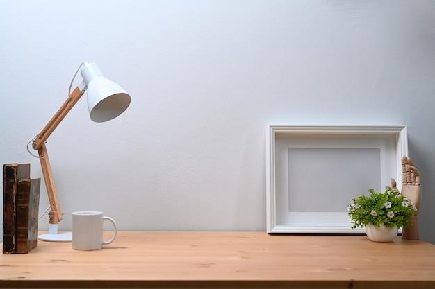 Pusta ramka na zdjęcia, roślina doniczkowa, lampa i książka na drewnianym stole.