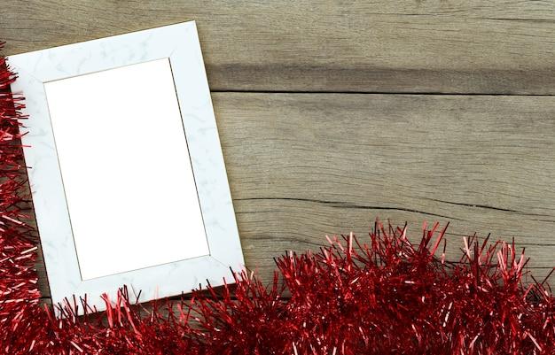 Pusta ramka na zdjęcia vintage na drewnianej podłodze i czerwone frędzle na dekoracje świąteczne i noworoczne