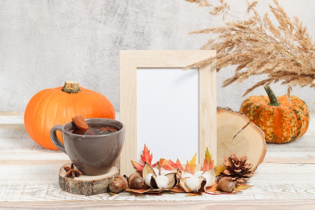 Pusta ramka na zdjęcia z jesiennymi dekoracjami i dyniami w tle