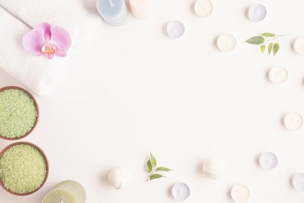 Pusta ramka otoczona miską ziołowych soli i świecami