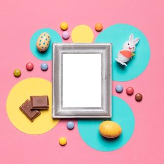 Pusta ramka otoczona pisankami; królik; cukierki i kawałki czekolady na różowym tle