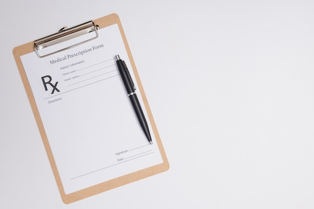 Pusta recepta lekarska z piórem na białym tle. długopis leżący na recepcie lekarskiej w pobliżu fonendoskopu w gabinecie lekarskim.