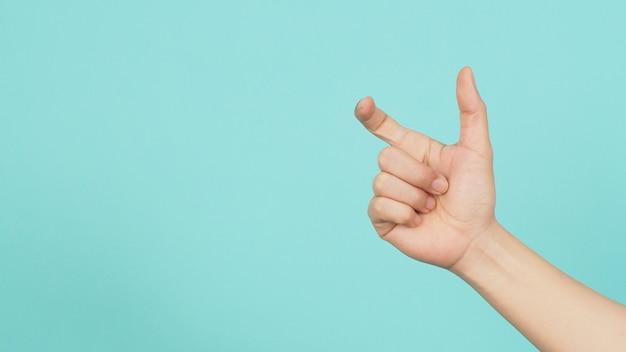 Pusta ręka trzyma lub łap nic gości na zielonym i niebieskim lub miętowym tle.