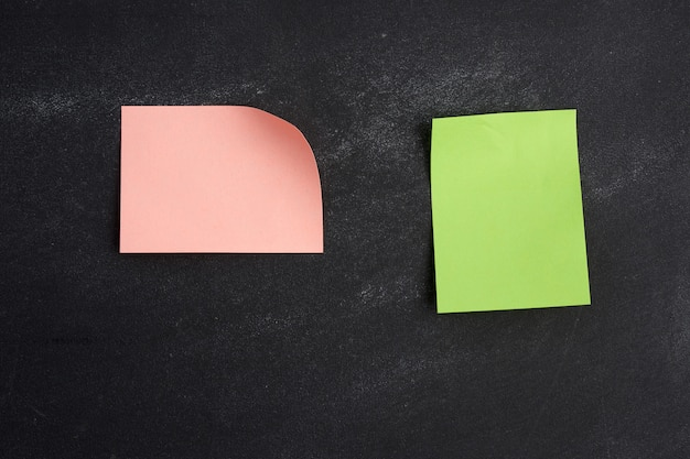 Pusta różowo-zielona naklejka z papieru przyklejona na czarnej desce