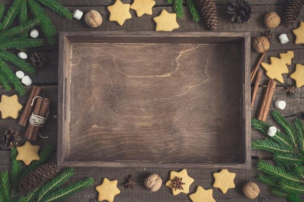 Pusta rustykalna taca otoczona herbatnikami imbirowymi, gałęziami i szyszkami jodły, cynamonem i orzechami włoskimi. boże narodzenie jedzenie tło.